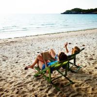 två tjer på stranden i solstolar